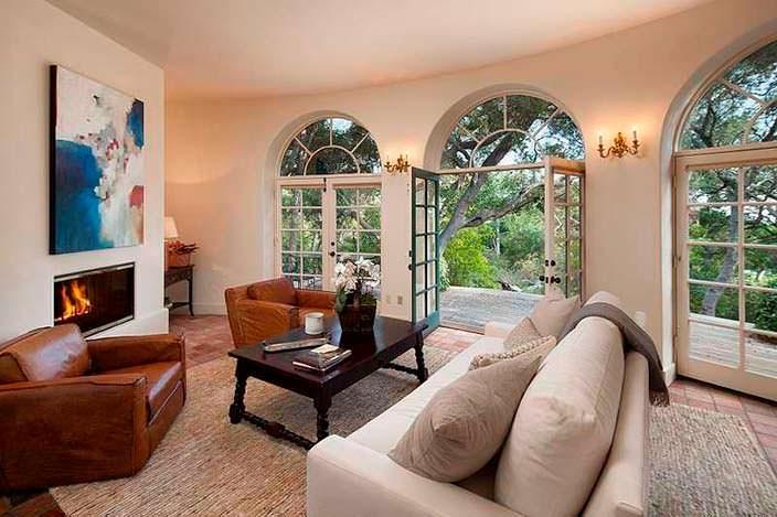 Дизайн комнаты с камином и панорамными окнами в сад