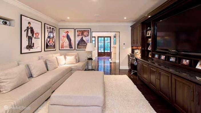 Огромный диван в дизайне комнаты с большим телевизором