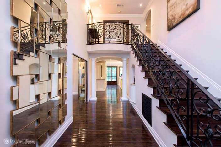 Лестница на второй этаж с коваными поручнями в доме Кардашьян