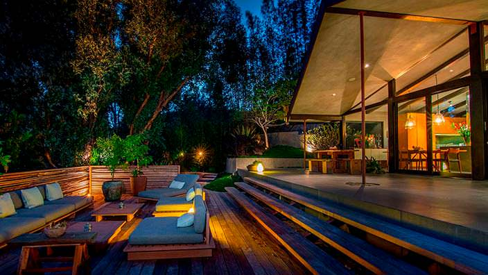 Деревянная терраса с уличной мебелью на заднем дворе дома