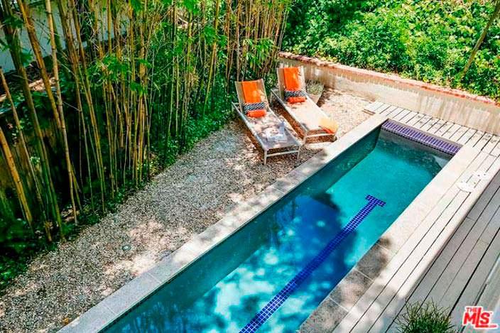 Бассейн и шезлонги на заднем дворе дома Винса Вона