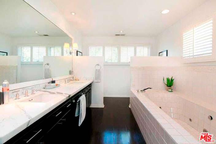 Ванная комната с мраморной столешницей и большим зеркалом