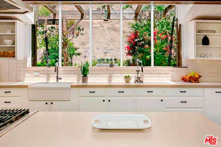 Панорамные окна на кухне с видом на задний двор с бассейном