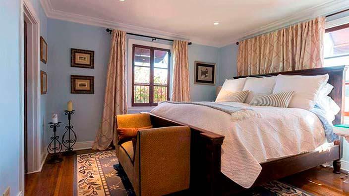 Высокая мягкая кровать в спальне в испанском стиле