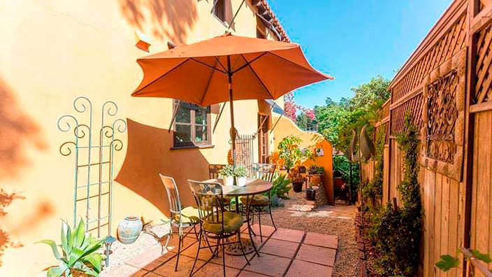 Дворик с кофейным столиком под зонтом у старого дома