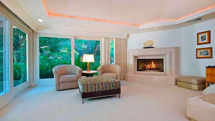 Спальня с камином и панорамными окнами на ранчо Джеки Коллинз