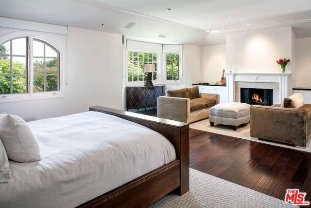 Спальня с деревянным полом и камином