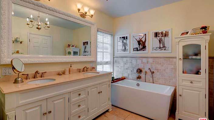 Ванная комната с большим зеркалом и ретро-мебелью