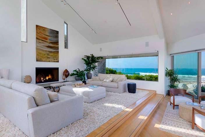 Современный дизайн гостиной с камином и видом на океан