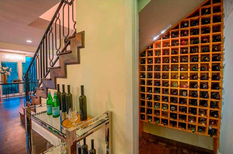 Винные полки под лестницей в доме