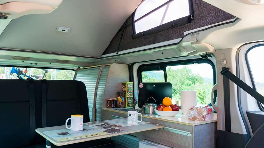Кухня с плитой, раковиной и холодильником в Nissan e-NV200 Camper