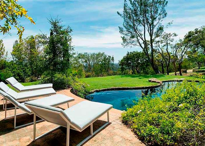 Шезлонги у бассейна и газона на участке дома в Монтесито