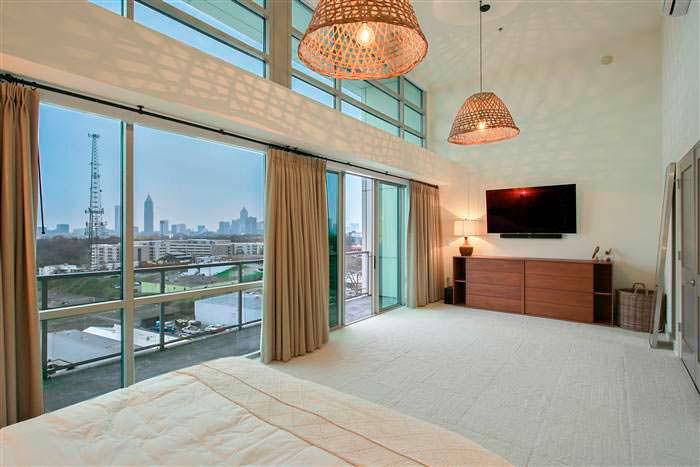 Дизайн спальни с панорамным окном и выходом на балкон