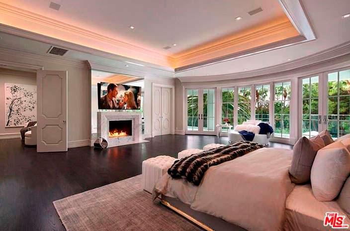 Огромная спальня в современном стиле с мраморным камином