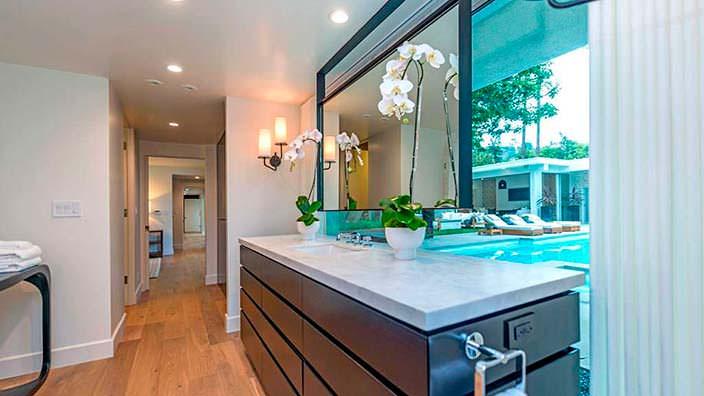 Ванная комната со стеклянной стеной и видом на бассейн