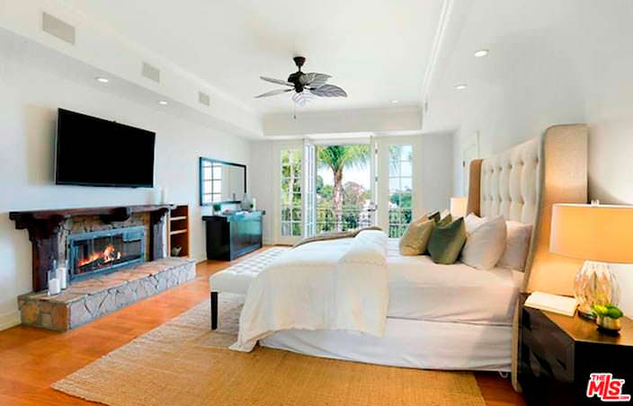 Спальня с большим камином и телевизором