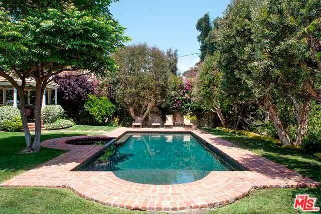 Бассейн на заднем дворе дома в тени деревьев