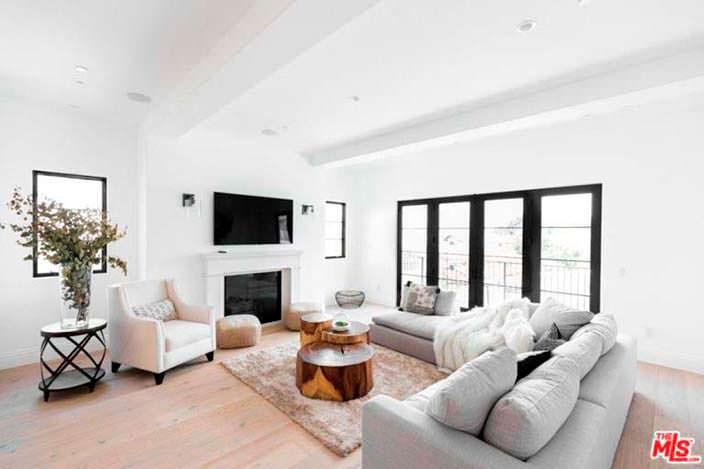 Белая гостиная с камином и телевизором