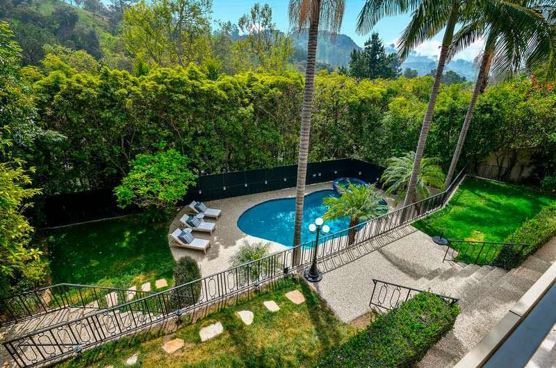 Плавательный бассейн и пальмы у дома